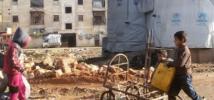 Des enfants remplissent des bidons à un point d'eau public dans le quartier de Tishreen, à Alep-Ouest.