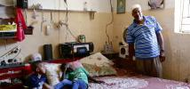Abu Amir with his children inside their home, pointing out the cracks in the walls, caused during the 2014 conflict. Photo: Alison M. Martin/Oxfam