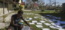 A teacher dries books in the sun after Cyclone Pam in Vanuatu