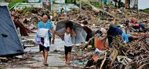 A woman and a child walk among the rubble in a village in Eastern Samar, after the typhoon Haiyan hit the Philippines. Credit: Jire Carreon/Oxfam