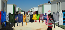 Boy walks past washing line Zaatari Refugee Camp