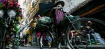 A woman cycles to work in Hanoi. Photo credit: Dewald Brand, Miran for Oxfam