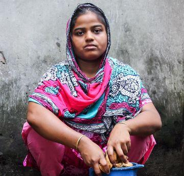Rasheda (24), a young mother-of-two, washes clothes in her yard, beside an open sewer, Chittagong, Bangladesh. Despite economic growth, almost 40 million people in Bangladesh still live below the national poverty line. Photo: GMB Akash/Oxfam