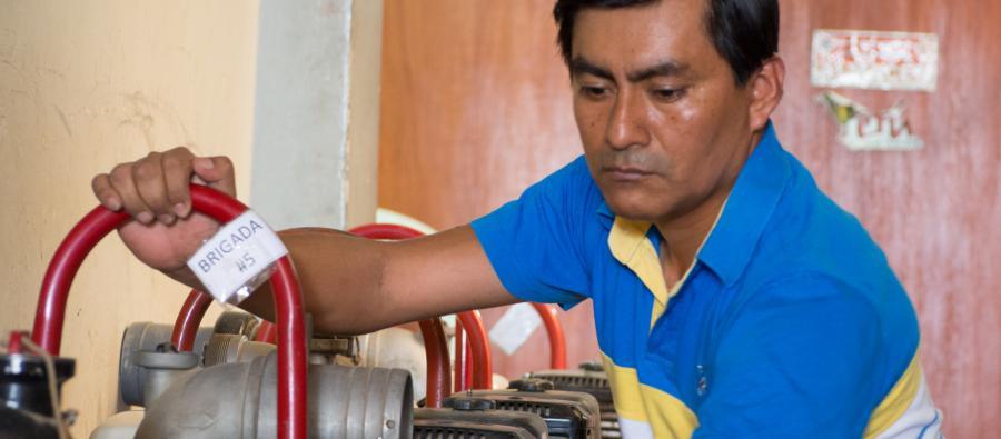 """Miguel Siesquen nettoie les pompes à eau achetées en prévision d'inondations. """"Il est important de renforcer nos moyens. Après tout, c'est nous qui vivons ici."""""""