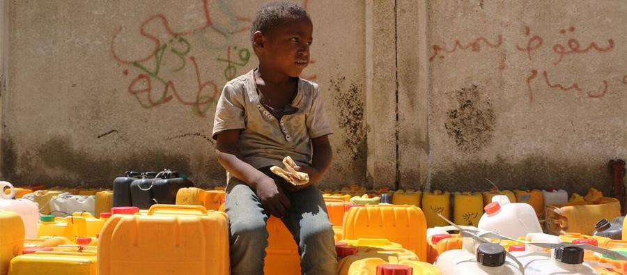A boy waits in line for water. He begs for food and is eating bread he got from a nearby bakery.