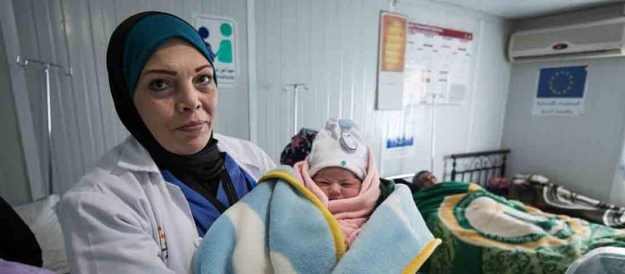 A doctor holds a new born baby, Za'atari Refugee Camp, Jordan