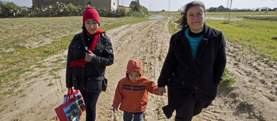 Ahlem Ben Ahmend walks home with her son through the fields on a windy day after visiting the HealthCare Centre in the local village Azmoure, Tunisia.