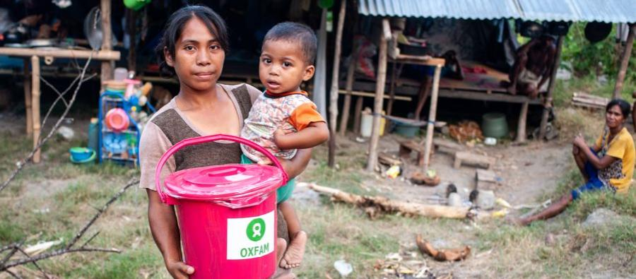Afrianti and her son at an Oxfam distribution of hygiene kits outside of Palu. The earthquake has displaced 88,000 people in sites that do not have adequate water and sanitation facilities. Photo: Hariandi Hafid/Oxfam