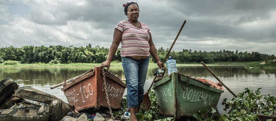 Todas las mañanas Jakeline transporta personas de una orilla a otra del río ya que no existen puentes ni otro tipo infratestructura segura para el desplazamiento en esta zona de Santo Domingo, República Dominicana. Foto: Pablo Tosco/Oxfam