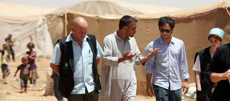 Gael Garcia Bernal talking with Hussein al-Muhammad, a resident of the tented settlement in Tneib, south of Amman