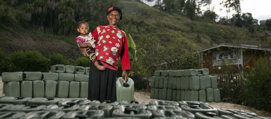 Elena Guma with her child. Oxfam and local partner organizations are distributing up to 6,500 jerry cans. Danbagl Village, Simbu Province, Papua New Guinea. Photo: Rodney Dekker/Oxfam