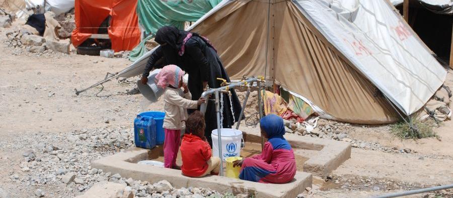 Une femme et des enfants prennent de l'eau potable à la rampe de distribution installée par Oxfam dans un camp pour personnes déplacées, à Huth. Photo : Kate Wiggans/Oxfam
