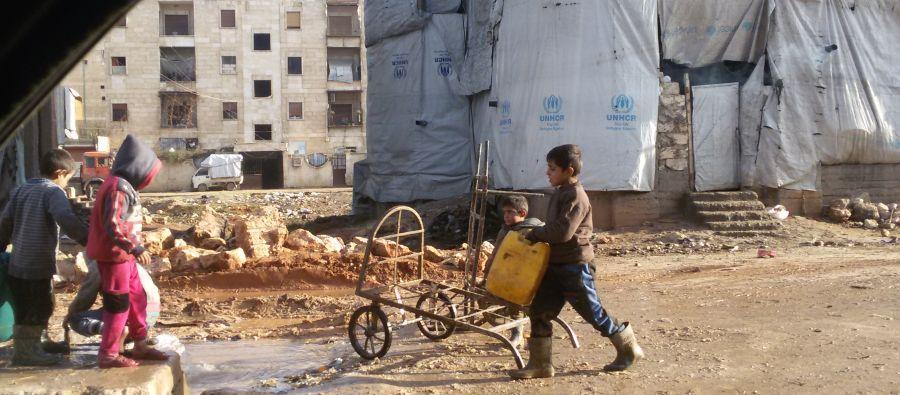Des enfants remplissent des bidons à un point d'eau public dans le quartier de Tishreen, à Alep-Ouest. Beaucoup sont des déplacés qui vivent dans des bâtiments en construction sans eau courante ni sanitaires.