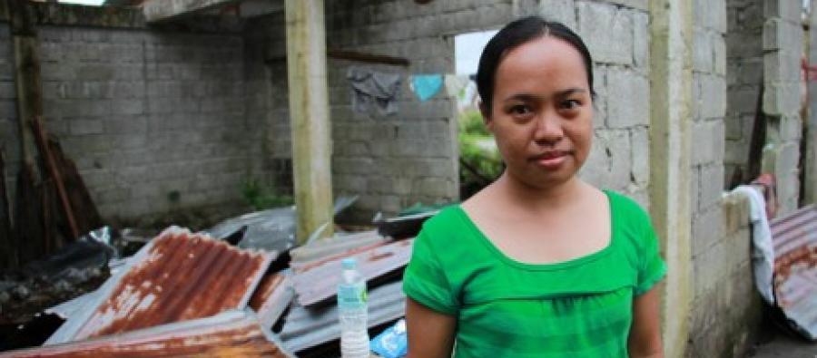 Rowena enfrente de su casa destruida. Foto: Anne Wright / Oxfam