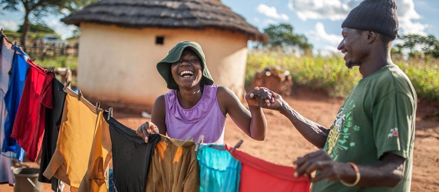 Ulita Mutambo's husband Muchineripi Sibanda helps her hang up laundry outside their home in Ture Village, Zvishevane region, Zimbabwe. Aurelie Marrier d'Unienville / Oxfam
